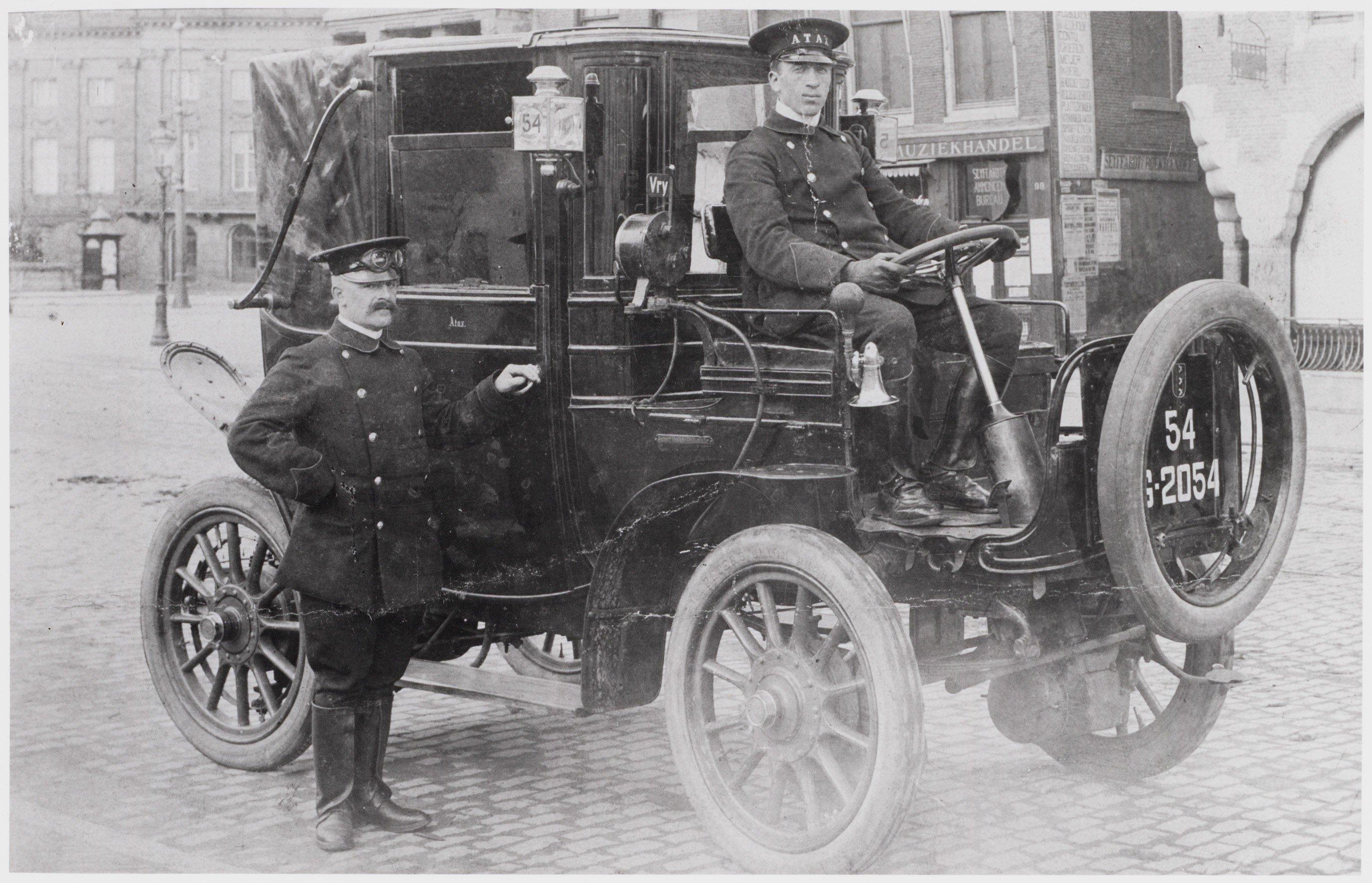Staxi Taxi geschiedenis - De heer H.F. Koek achter het stuur van een Atax op het Damrak